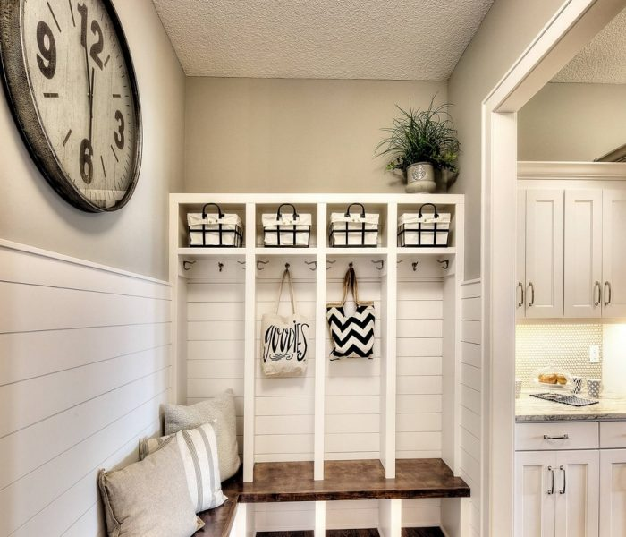 shaker style mudroom cabinetry in white with dark stained wood bench