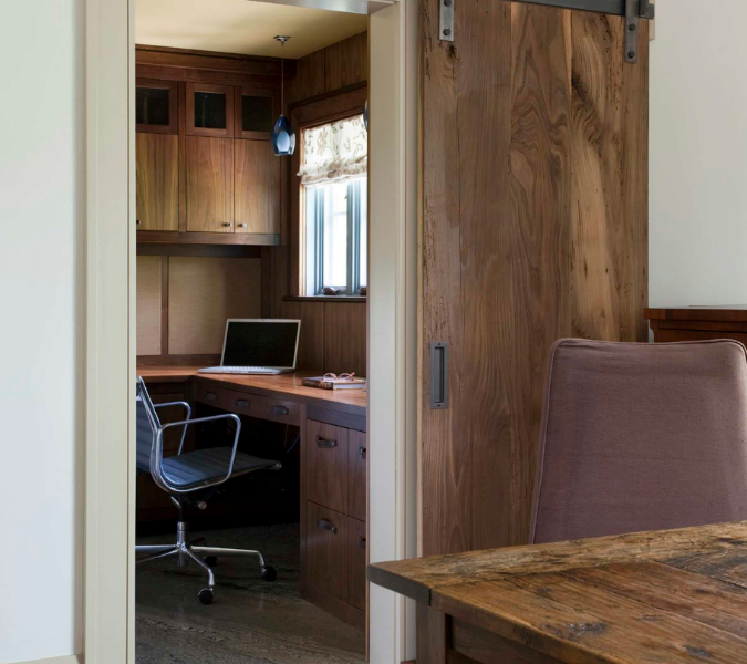 transitional style office with barn door in natural wood stain