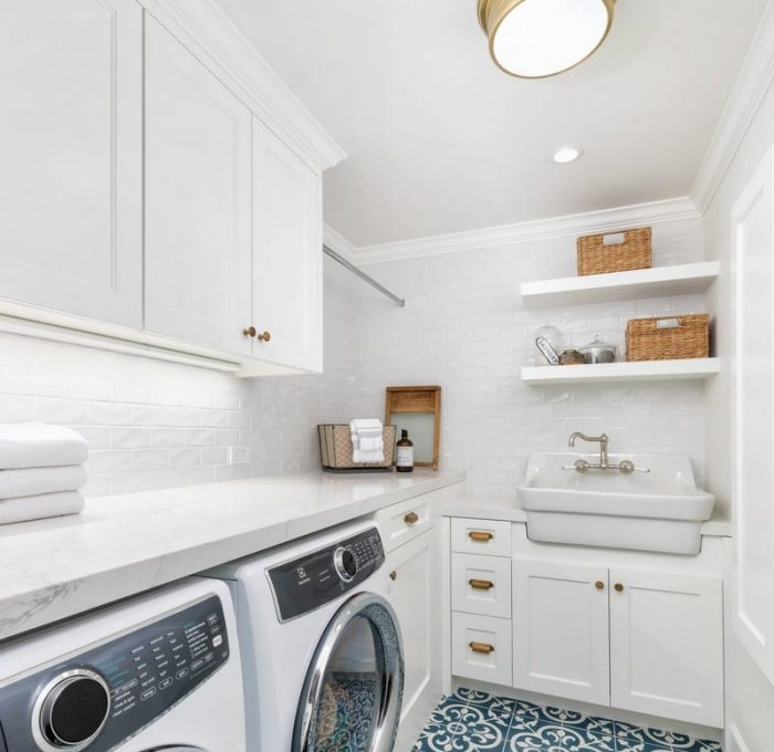 shaker style laundry cabinetry in white with blue tile floor