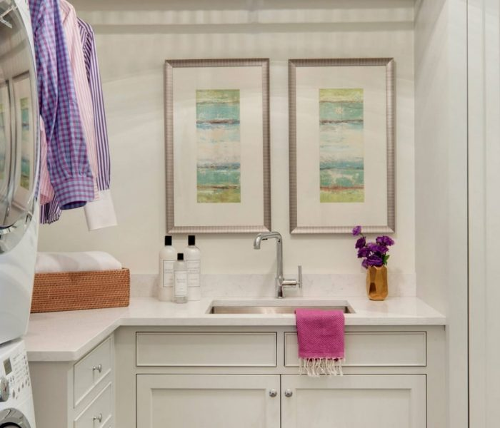 traditional white laundry room cabinetry with hanging rod