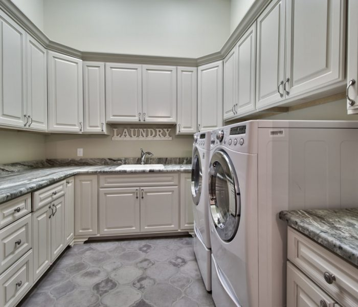 traditional style laundry room in white with quartz cabinetry and quartz countertops